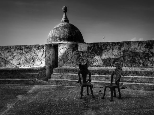 A pair of  artisan-crafted, metal chairs sit in front of one of the historic walls of Old San Juan, Puerto Rico.