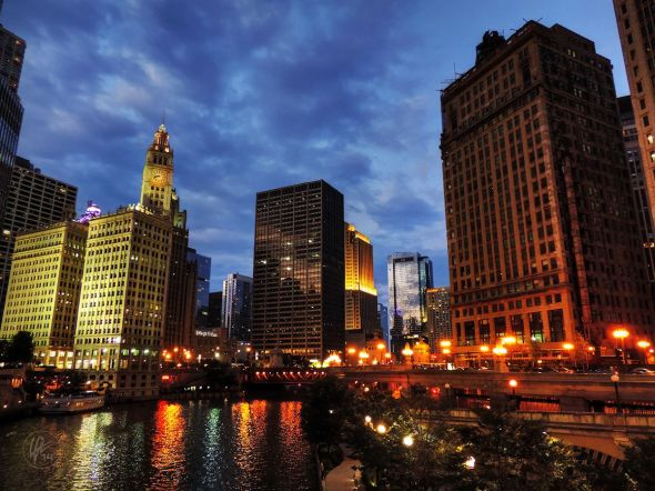 As you stand on the Wabash Ave. (Irv Kupcinet) Bridge at twilight, you can see the reflection of the Wrigley Building and the other buildings in the Wacker - Michigan Historic District in the waters of the Chicago River in Downtown Chicago, IL.