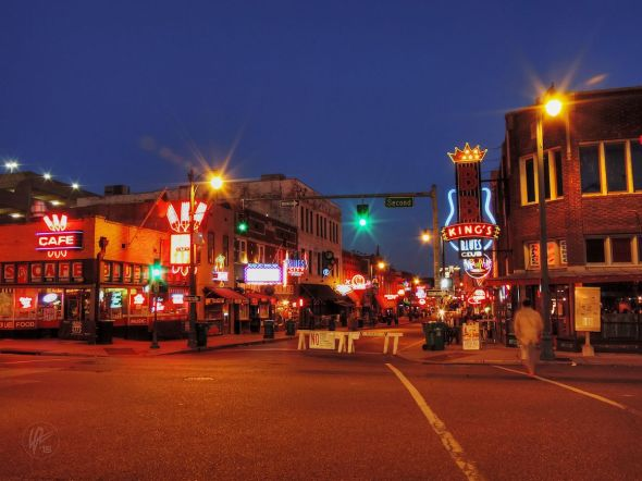 After sunset, the sky still has a deep blue glow that contrasts the warm, amber tones of the street lamps and neon signs on Beale St. in Memphis, TN.