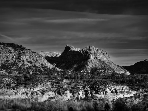 The sunlight casts dark shadows on the rock formations of the desert in Springdale, UT.