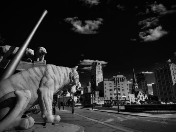 Tiger statues at the entrance of Comerica Park look out to the cityscape of Downtown Detroit, MI.